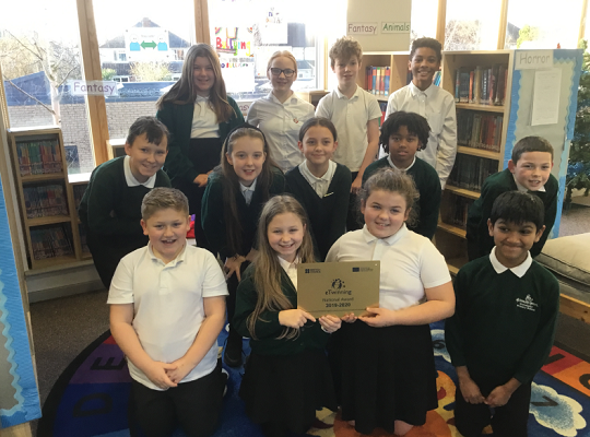Children at Alderman's Green Community Primary show off the award