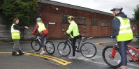 Three people being trained to cycle safely.
